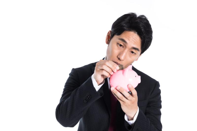 貯金箱に小銭を入れるサラリーマン