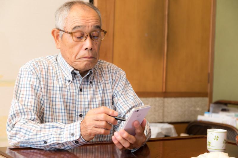 慣れない手つきでスマホを弄る高齢のお爺さん